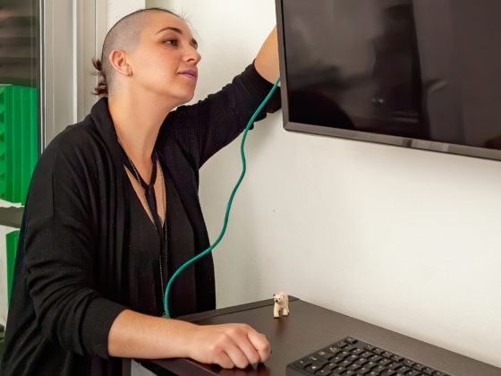 large-scale infrastructure, woman plugging cable into a tv